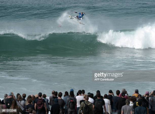 People watch as a competitor surfs a wave during the final of the French stage of the World Surfing Championship 2017 Quiksilver Pro France in...