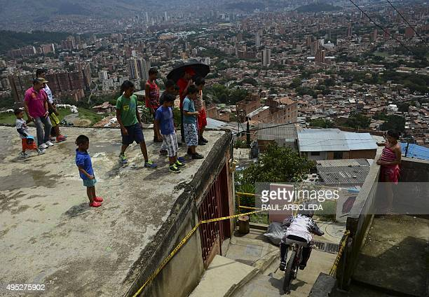 People watch as a downhill rider competes during the Adrenalina Urban Bike race final at the Comuna 13 shantytown in Medellin Antioquia department...