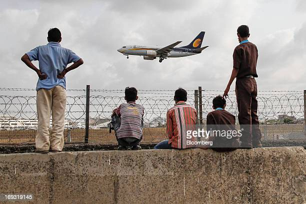 People watch as a Jet Airways Ltd aircraft prepares to land at Chhatrapati Shivaji International Airport in Mumbai India on Thursday May 23 2013 Jet...