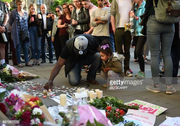 People watch as a man and a child light a candle alongside floral tributes in Albert Square in Manchester northwest England on May 23 following a...