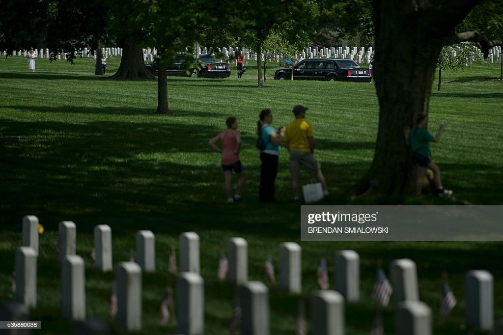 People watch as a motorcade with US President Barack Obama leaves after an event to honor Memorial Day at Arlington National Cemetery May 30, 2016 in Arlington, Virginia. / AFP / Brendan Smialowski