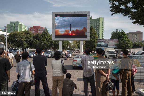 TOPSHOT People watch as a screen shows footage of the launch of a Hwasong12 rocket beside a billboard advertising North Korea's Pyeonghwa Motors in...
