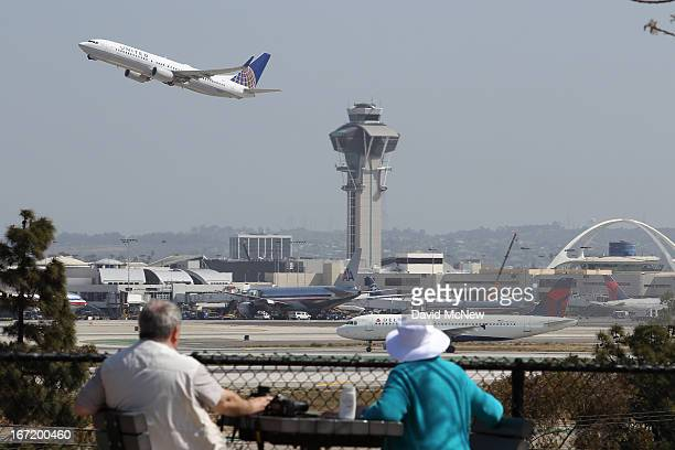 People watch as a United Airlines jet passes the air traffic control tower at Los Angles International Airport during takeoff on April 22 2013 in Los...