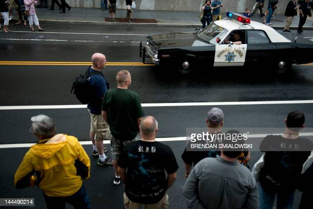 People watch as a vintage California Highway Parole car drives by May 14 2012 in Washington DC Police and emergency workers from around the United...