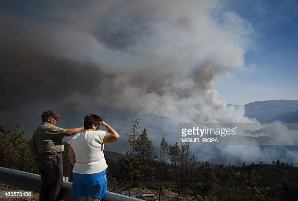 People watch as a wildfire burns next the village of Cobas close Vilanova de Cerveira northern Portugal on August 10 2015 Nearly 1000 firefighters as...