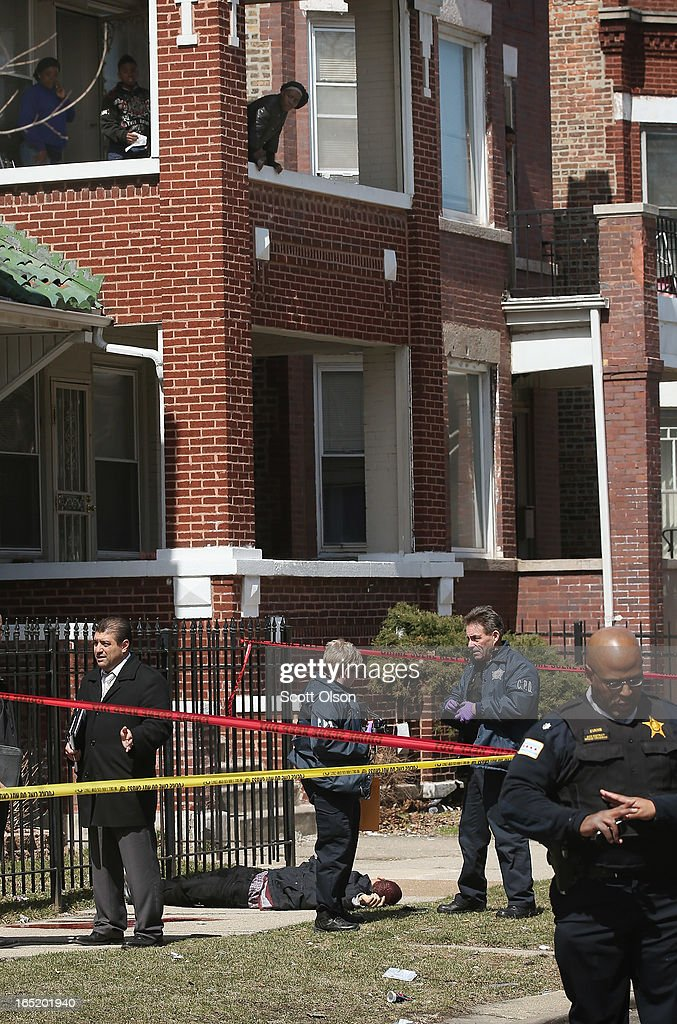 People watch as Chicago police investigate the murder of a 24-year-old man who was shot and killed on South Eberhart Avenue on the city's South Side April 1, 2013 in Chicago, Illinois. According to published reports, the man was the 73rd homicide victim and the 39th victim under the age of 25 in Chicago in 2013.