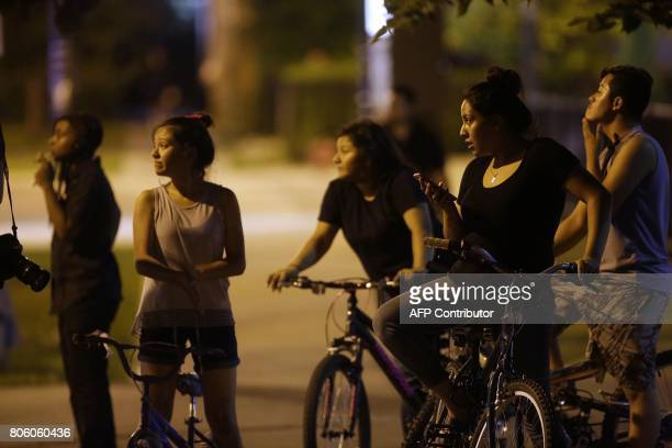 People watch as Chicago Police officers investigate the crime scene where a man was shot in the alley in the Little Village neighborhood on July 2...