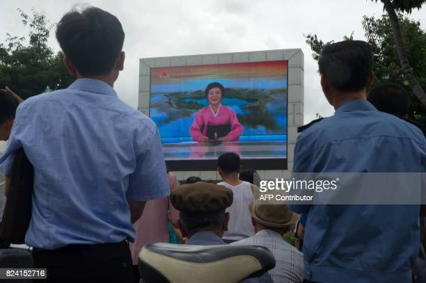People watch as coverage relating to an ICBM missile test is displayed on a screen in a public square in Pyongyang on July 29 2017 Kim JongUn boasted...