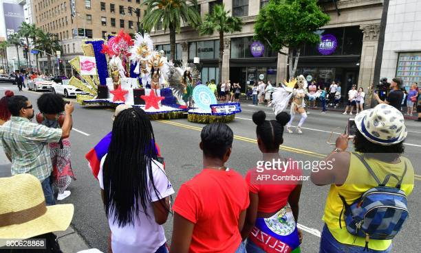 People watch as dancers make their way down Hollywood Boulevard for the 6th annual Hollywood Carnival Parade celebrating world cultures on June 24...
