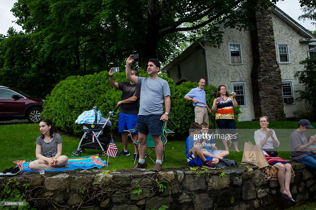 People watch as Democratic presidential candidate former Secretary of State Hillary Clinton, former President Bill Clinton and New York Governor Andrew M. Cuomo walk in the Memorial Day parade May 30, 2016 in Chappaqua, New York.