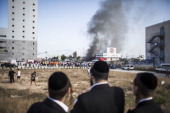 People watch as firefighters try to douse a fire from a rocket that hit a Petrol station on July 11 2014 in Ashdod Israel The Israeli army are into...