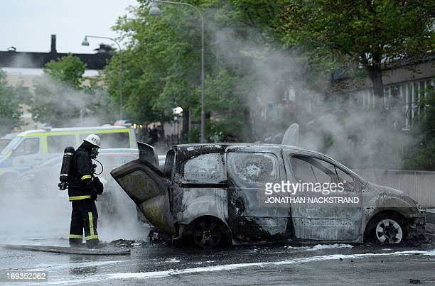 People watch as firemen extinguish burning cars in the Stockholm suburb of Rinkeby after youths rioted in several different suburbs around Stockholm...