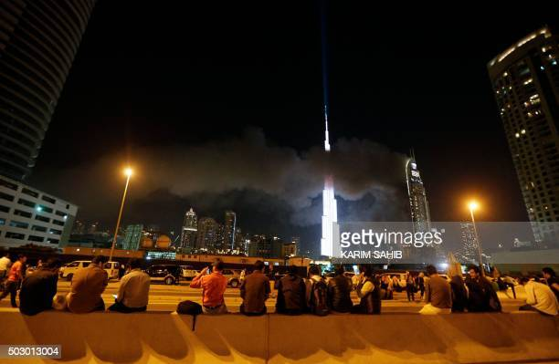 People watch as flames rip through the Address Downtown hotel after it was hit by a massive fire near the world's tallest tower Burj Khalifa in Dubai...