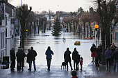 People watch as flooding blights the market town of Cockermouth at the confluences of the River Cocker and River Derwent which are overflowing with...