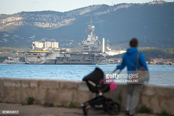 People watch as French aicraft carrier 'Charles de Gaulle' on December 14 2016 as it returns to the French naval base of Toulon southern France after...