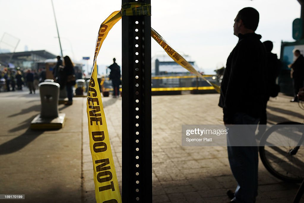 People watch as injured passengers are aided following an early morning ferry accident during rush hour in Lower Manhattan on January 9, 2013 in New York City. About 50 people were injured in the accident, which left a large gash on the front side of the Seastreak ferry at Pier 11.