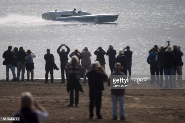 People watch as Karl FoulkesHalbard pilots the restored Blue Bird K3 hydroplane powerboat during a test run at Bewl Water on September 26 2017 near...