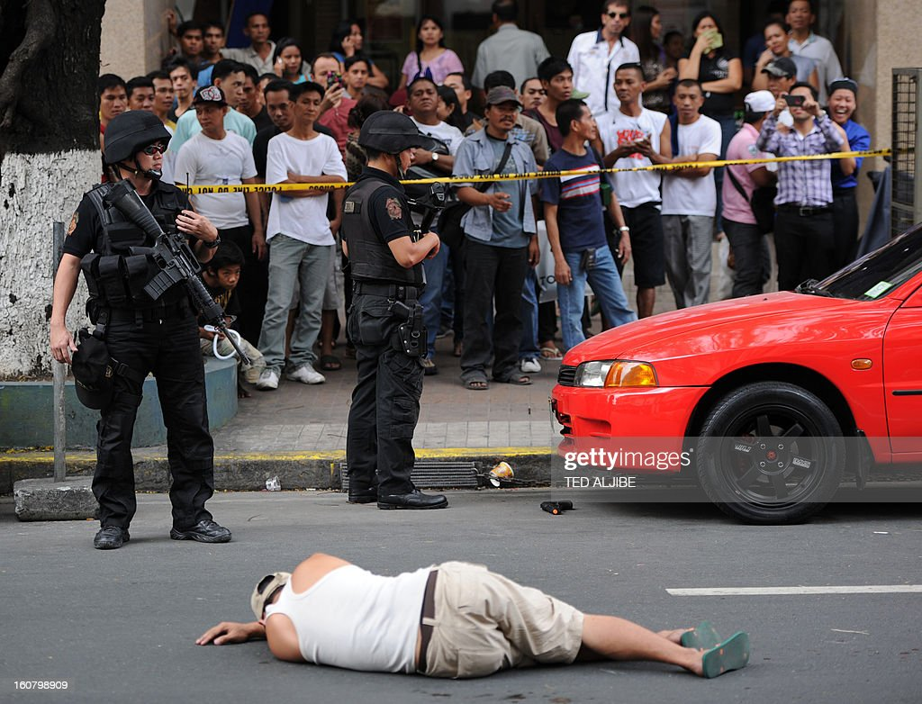 People watch as members of SWAT team stand guard next to a man acting as a robber lying on a road during a shopping mall robbery simulation in Manila on February 6, 2013, as part of heightened security and police visibility after recent attacks at shopping centres. Police have stepped up their visibility and security in response to recent attacks in popular Manila shopping malls, including the ransacking of a mall jewellery store on January 26.