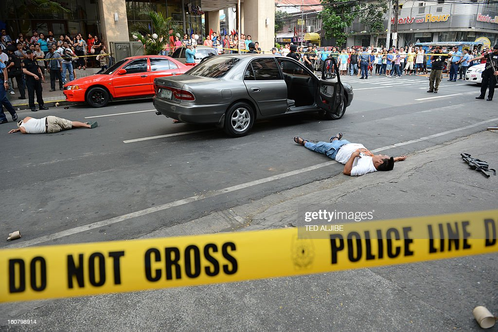 People watch as members of SWAT team stand guard next to men acting as robbers lying on a road during a shopping mall robbery simulation in Manila on February 6, 2013, as part of heightened security and police visibility after recent attacks at shopping centres. Police have stepped up their visibility and security in response to recent attacks in popular Manila shopping malls, including the ransacking of a mall jewellery store on January 26.