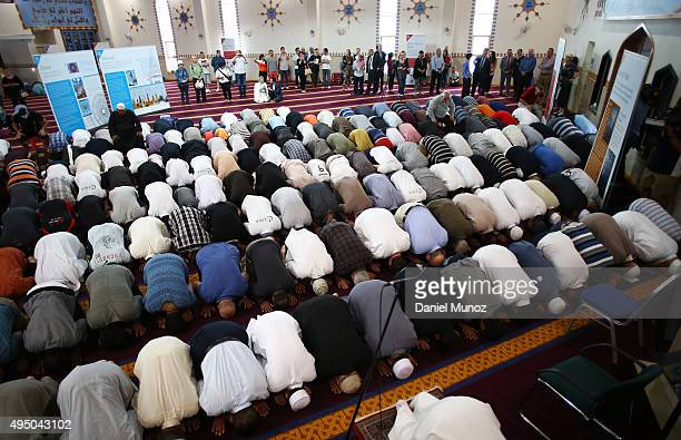 People watch as Muslims attend the noon prayer during an open day at Lakemba Mosque on October 31 2015 in Sydney Australia Mosques held open days...