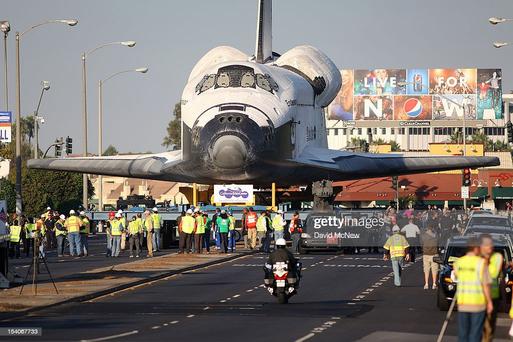 People watch as NASA space shuttle Endeavour moves along Manchester Avenue as it is transported from Los Angeles International Airport (LAX) to the California Science Center in Exposition Park where it will be on permanent public display on October 13, 2012 in Inglewood, California. Endeavour was flown cross-country atop NASA's Shuttle Carrier Aircraft from Kennedy Space Center in Florida to LAX on its last flight ever on September 21. Completed in 1991, Endeavour was built to replace the space shuttle Challenger which disintegrated during a catastrophic re-entry accident. This fifth and final space shuttle orbiter circled the earth 4,671 times and traveled nearly 123 million miles during its 25 missions from 1992 to 2011.