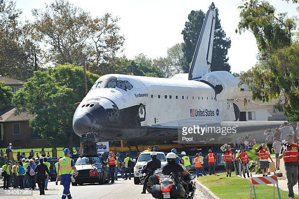 People watch as NASA Space Shuttle Endeavour moves on Crenshaw Drive enroute to the California Science Center on October 13 2012 in Inglewood...