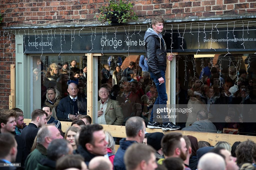 People watch as opposing teams, the Up'ards and the Down'ards, take part in the annual Royal Shrovetide Football Match in Ashbourne, northern England, on February 9, 2016. The mass-participation ball game involves two teams, whose players are defined by which side of a small brook that bisects the town they were born, aiming to score a goal, which are some three miles apart. The game, which has very few rules, is played over two 8 hour periods on Shrove Tuesday and Ash Wednesday. Royal Shrovetide Football is believed to have been played annually in Ashbourne since 1667. / AFP / OLI SCARFF