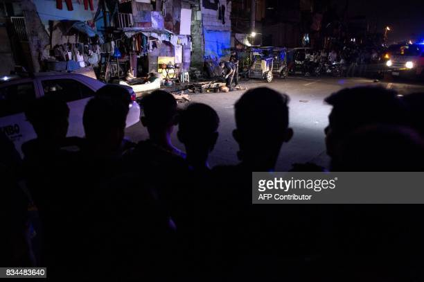 People watch as police officers investigate the dead body of an alleged drug dealer killed during a police antidrug operation in Manila on August 18...