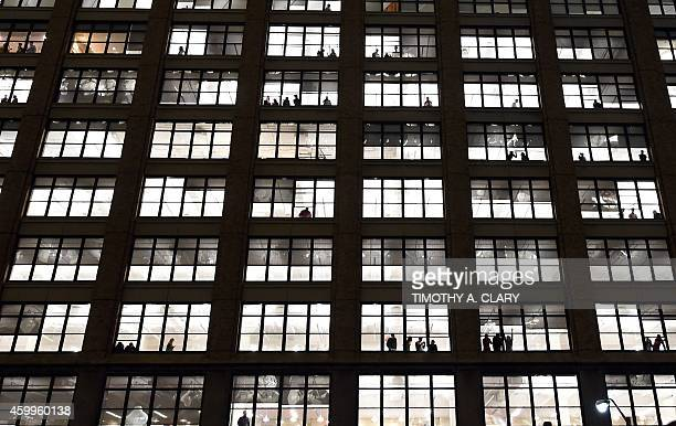 People watch as protesters walk pass their building in New York City on December 4 2014 during demonstration against the chokehold death of an...