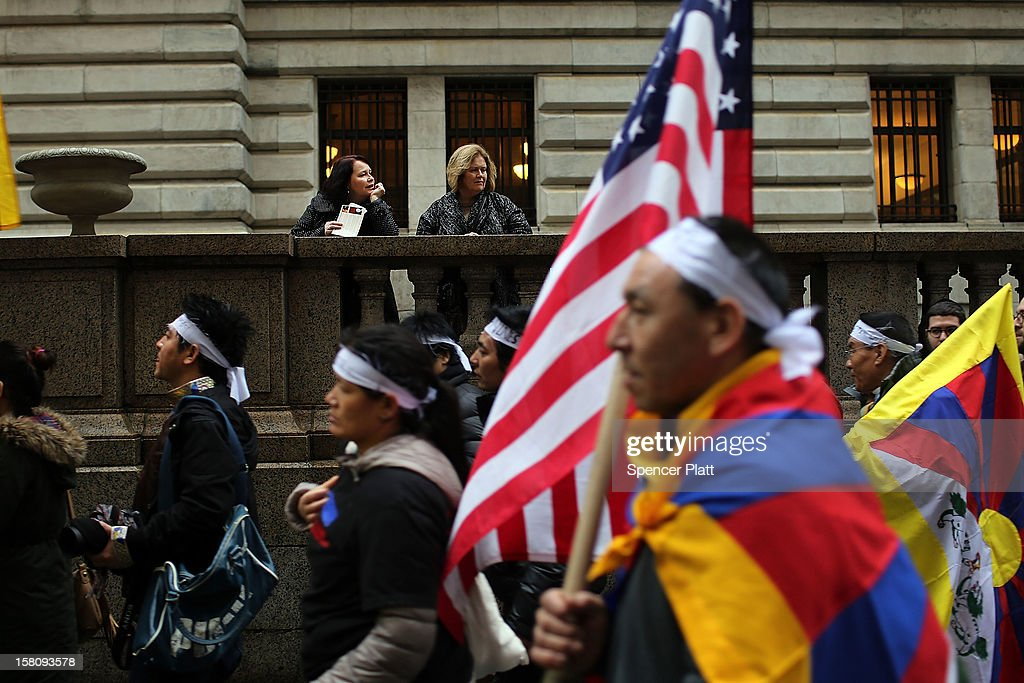 People watch as protestors march down 42nd street to the United Nations General Assembly Building in recognition of International Human Rights Day on December 10, 2012 in New York City. Chinese-occupied Tibet has witnessed over 90 Tibetans self-immolating themselves in protest to China since 2009. Tibetans, their supporters and human rights activists are calling for immediate action by the United Nations and world governments to pressure China to resolve the issue.