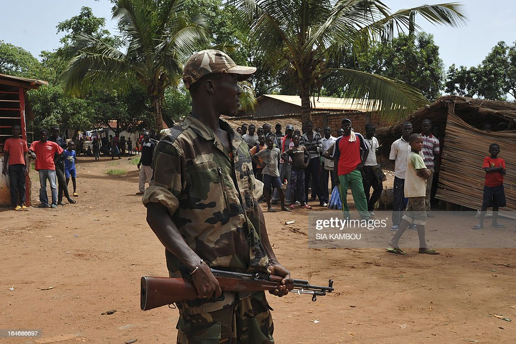 People watch as rebels of the Seleka coalition arrive to arrest people suspected of looting in a neighbourood of Bangui on March 26, 2013. Central African Republic strongman Michel Djotodia was set to unveil a new government on March 26 after declaring he would rule by decree following the latest coup in the notoriously unstable nation. Looters were on the rampage in the capital Bangui after Djotodia's Seleka rebel coalition seized control in a rapid-fire weekend assault that forced president Francois Bozize into exile and was condemned by the international community. AFP PHOTO / SIA KAMBOU