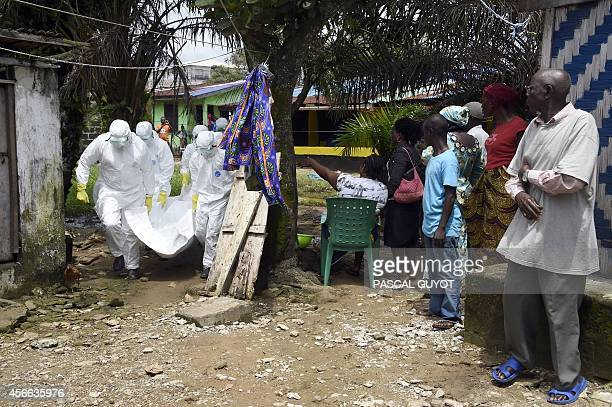 People watch as Red Cross workers carry away the body of a person suspected of dying from the Ebola virus in the Liberian capital Monrovia on October...