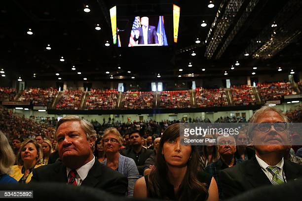 People watch as Republican presidential candidate Donald Trump speaks at a rally on May 26 2016 in Bismarck North Dakota According to a delegate...
