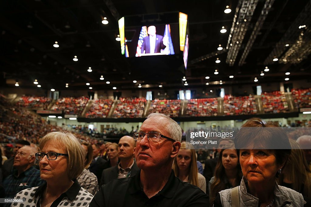 People watch as Republican presidential candidate Donald Trump speaks at a rally on May 26, 2016 in Bismarck, North Dakota. According to a delegate count released Thursday, Trump has reached the number of delegates needed to win the GOP presidential nomination.