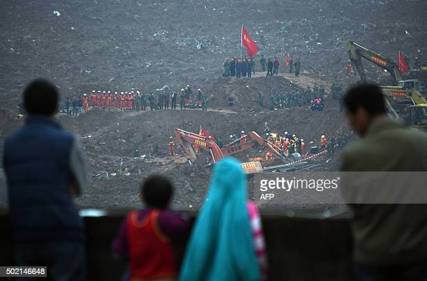TOPSHOT People watch as rescue workers look for survivors after a landslide hit an industrial park in Shenzhen south China's Guangdong province on...
