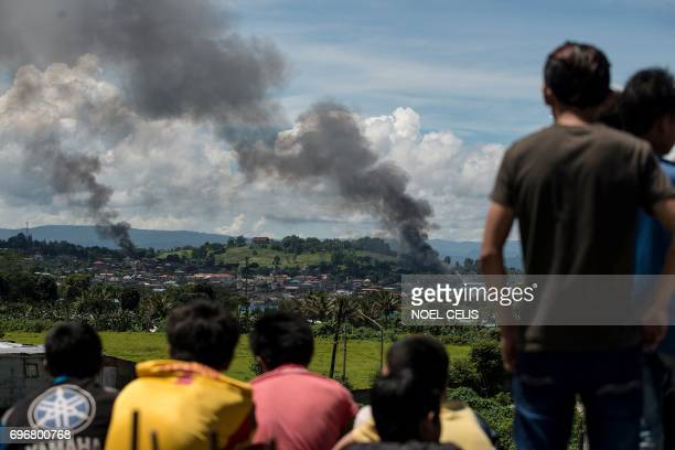 TOPSHOT People watch as smoke billows from houses after aerial bombings by Philippine Airforce planes on Islamist militant positions in Marawi on the...