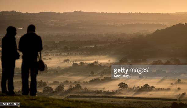 People watch as the autumn sun rises over the Somerset Levels viewed from Glastonbury Tor near Glastonbury on September 22 2017 in Somerset England...