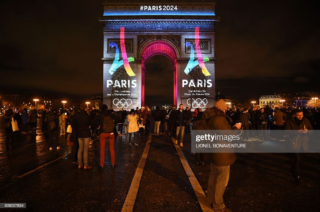 People watch as the campaign's official logo of the Paris bid to host the 2024 Olympic Games is seen on the Arc de Triomphe in Paris on February 9...