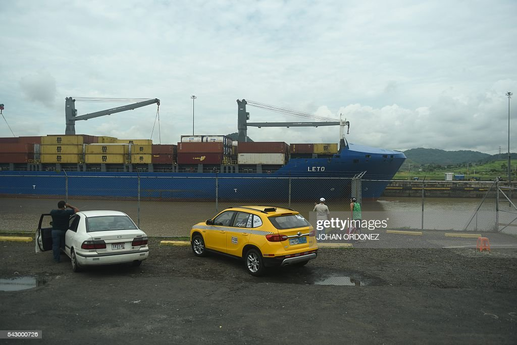 People watch as the cargo ship Leto Manrovia crosses the Miraflores Locks of the Panama Canal, in Panama City on June 25, 2016. Panama will officially open its canal on Sunday to far bigger cargo ships after nearly a decade of expansion work aimed at boosting transit revenues and global trade. On Sunday, a VIP ceremony will be held on the banks of the canal to inaugurate the completion of the works. / AFP / JOHAN
