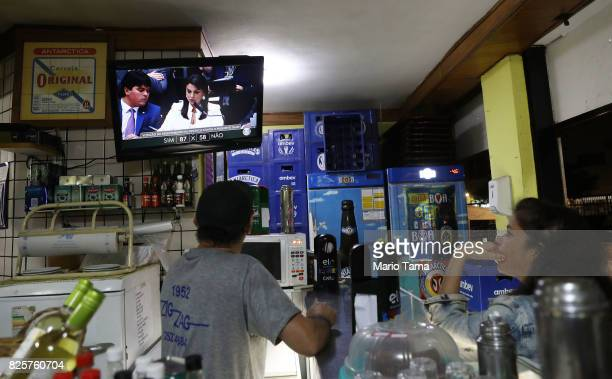 People watch as the congressional vote over President Michel Temer's bribery charge which could have suspended his presidency is played live on...