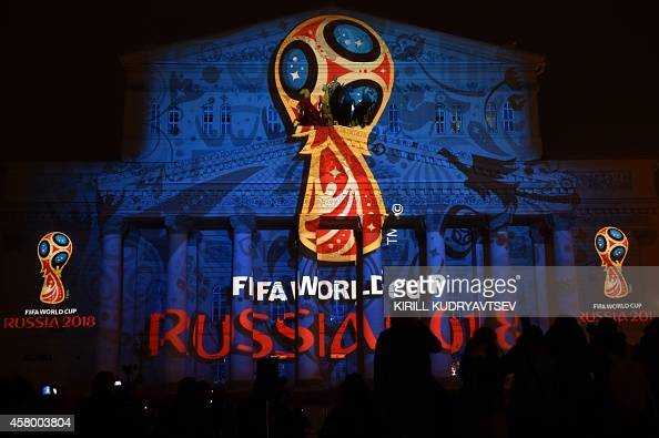 People watch as the facade of the historical Bolshoi Theatre is illuminated with the official emblem of the 2018 FIFA World Cup to be held in Russia...