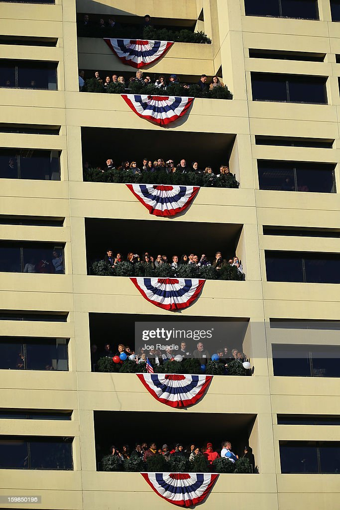 People watch as the inauguration parade passes by on January 21, 2013 in Washington, DC. President Barack Obama was ceremonially sworn in for a second term office during a public ceremony at the U.S. Capitol building.