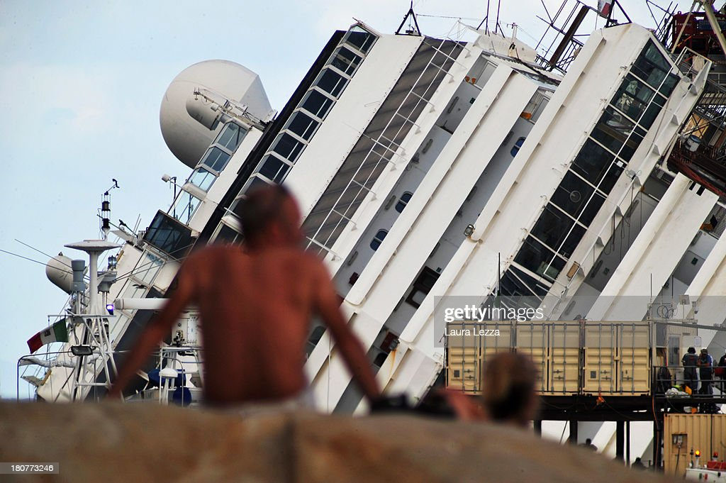 People watch as the parbuckling project to raise the stricken Costa Concordia continues on September 16, 2013 in Isola del Giglio, Italy. Work begins today to right the stricken Costa Concordia vessel, which sank on January 12, 2012. If the operation is successful, it will then be towed away and scrapped. The procedure, known as parbuckling, has never been carried out on a vessel as large as Costa Concordia before.