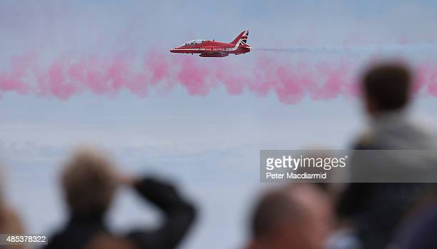 People watch as the RAF Red Arrows display team takes part in the Clacton Airshow on August 27 2015 in ClactononSea England This is the first public...