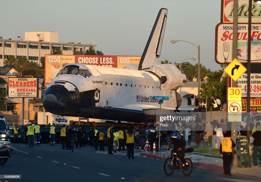 People watch as the Space Shuttle Endeavour is slowly moved along Manchester Blvd. enroute to the California Science Center on October 13, 2012 in Inglewood, California. Endeavour is on its last mission - a 12-mile creep through city streets, past an eclectic mix of strip malls, mom-and-pop shops, tidy lawns and faded apartment buildings. Its final destination is the California Science Center in South Los Angeles where it will be put on display. NASA's Space Shuttle Program ended in 2011 after 30 years and 135 missions.