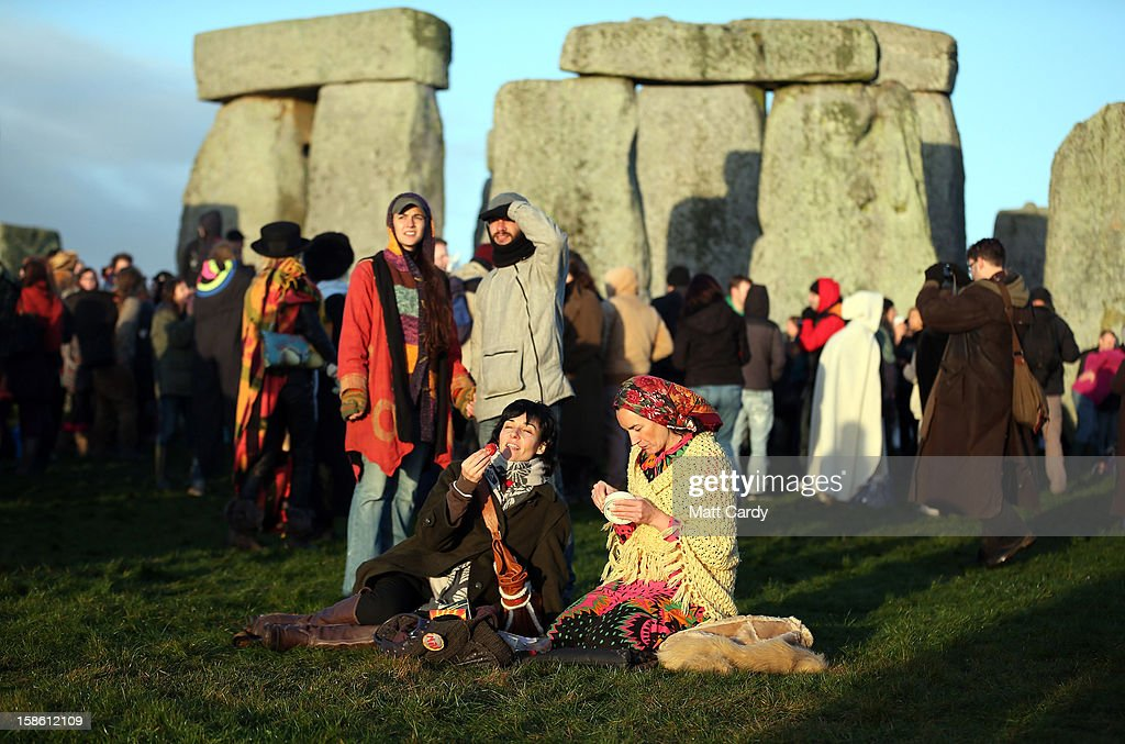 People watch as the sun rises as druids, pagans and revellers take part in a winter solstice ceremony at Stonehenge on December 21, 2012 in Wiltshire, England. Predictions that the world will end today as it marks the end of a 5,125-year-long cycle in the ancient Maya calendar, encouraged a larger than normal crowd to gather at the famous historic stone circle to celebrate the sunrise closest to the Winter Solstice, the shortest day of the year.