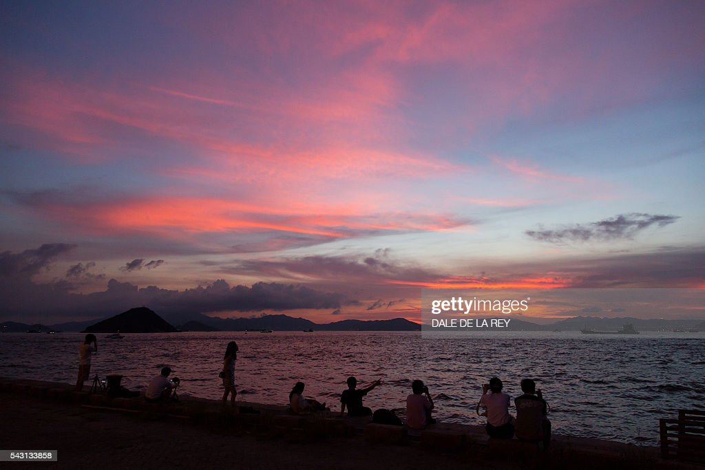 People watch as the sun sets over Victoria Harbour in Hong Kong on June 26, 2016. The official Hong Kong Observatory issued a hot weather warning on June 26 as a subtropical ridge continued to bring very hot weather to southern China. / AFP / DALE