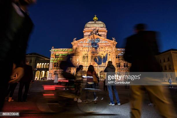 People watch as the Swiss House of Parliament is illuminated during a light show entitled 'Rendezvous Bundesplatz' in the Swiss capital Bern on...