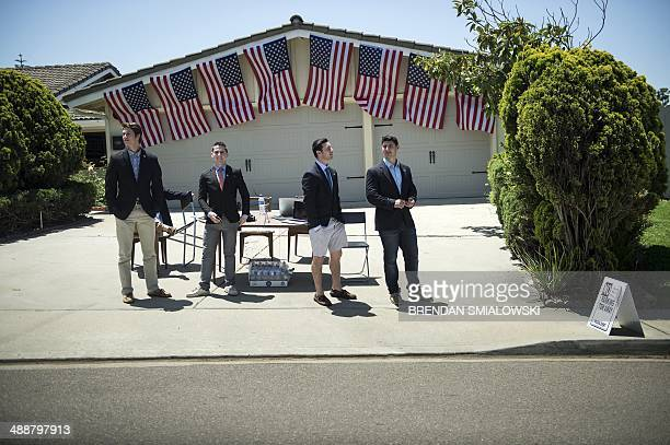 People watch as US President Barack Obama motorcade passes while arriving at Qualcomm founder Irwin M Jacobs's home on May 8 2014 in La Jolla...
