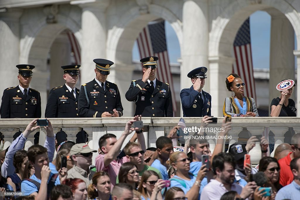 People watch as US President Barack Obama places a wreath at the Tomb of the Unknowns to honor Memorial Day at Arlington National Cemetery May 30, 2016 in Arlington, Virginia. / AFP / Brendan Smialowski